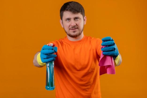 Giovane uomo che indossa maglietta arancione e guanti di gomma che tengono spray per la pulizia e tappeto sorridente fiducioso