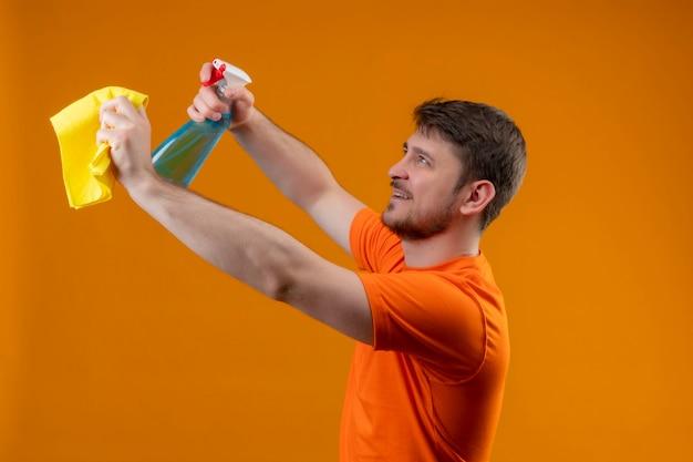 Giovane uomo che indossa maglietta arancione e guanti di gomma che tengono spray per la pulizia e tappeto in piedi lateralmente