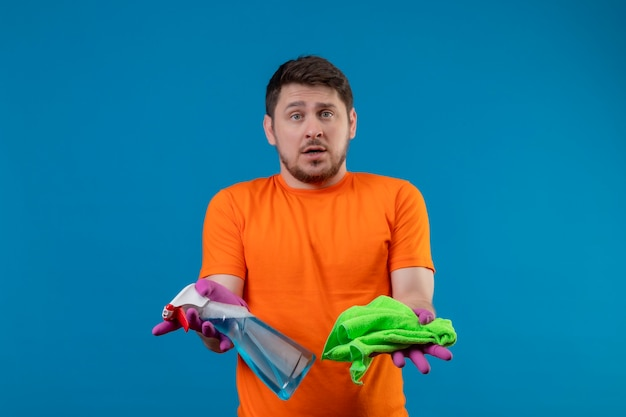 Young man wearing orange t-shirt and rubber gloves holding cleaning spray and rug