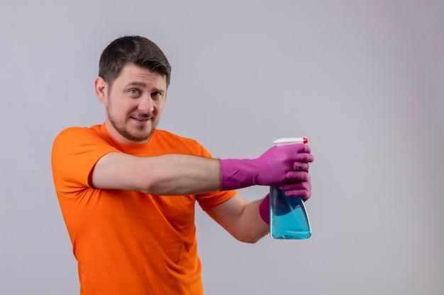Giovane uomo che indossa la maglietta arancione e guanti di gomma che tengono spray per la pulizia sorridente utilizzando spray in piedi sul muro bianco