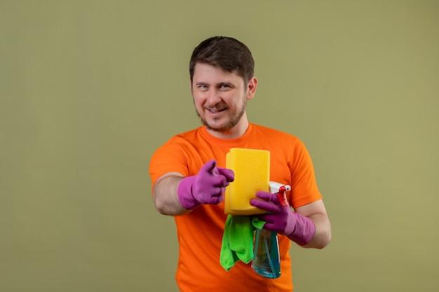 Giovane uomo che indossa maglietta arancione e guanti di gomma che tengono spray per la pulizia e spugna sorridendo felice e positivo che punta con il dito alla fotocamera in piedi sopra la parete verde