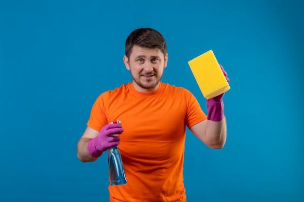 Giovane uomo che indossa maglietta arancione e guanti di gomma che tengono spray per la pulizia e spugna
