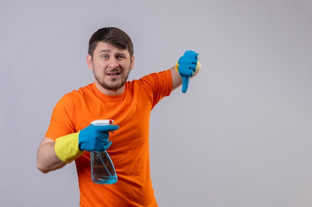 Young man wearing orange t-shirt and rubber gloves holding cleaning spray with sad expression