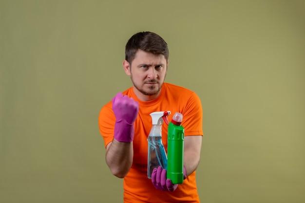 Giovane uomo che indossa maglietta arancione e guanti di gomma che tengono i prodotti per la pulizia cercando fiducioso pugno di serraggio con espressione seria sul viso pronto a pulire il concetto in piedi sopra la parete verde