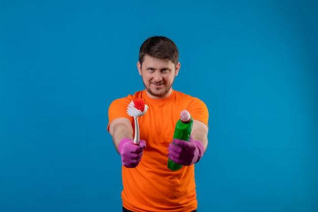Giovane che indossa la maglietta arancione e guanti di gomma che tengono i prodotti per la pulizia e la spazzola che sorride in piedi positivo e felice sopra la parete blu