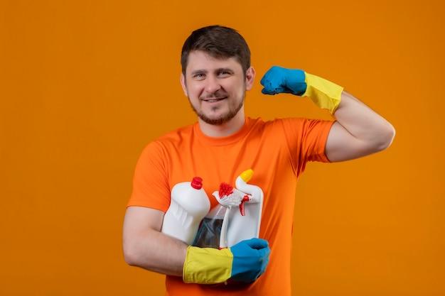 Giovane uomo che indossa la maglietta arancione e guanti di gomma tenendo i prodotti per la pulizia sorridendo allegramente positivo e felice guardando la telecamera che mostra il bicipite pronto per pulire il concetto su sfondo arancione