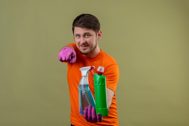 Young man wearing orange t-shirt and rubber gloves holding cleaning supplies smiling positive and happy pointing with finger to camera standing over green wall 2