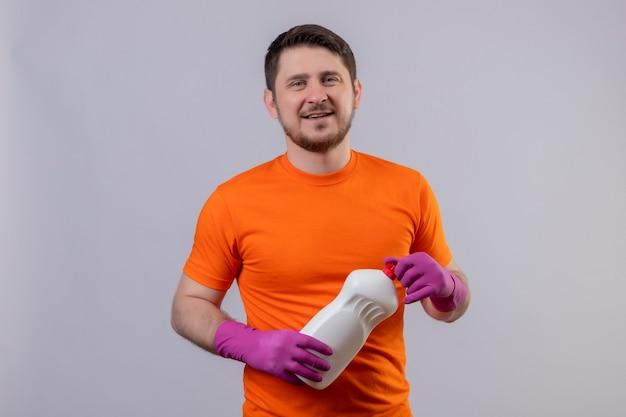 Giovane che indossa la maglietta arancione e guanti di gomma che tengono i rifornimenti di pulizia che sorridono in piedi positivo e felice sopra il muro bianco