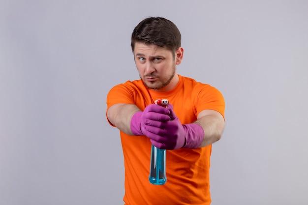 Giovane uomo che indossa maglietta arancione e guanti di gomma che tengono i prodotti per la pulizia