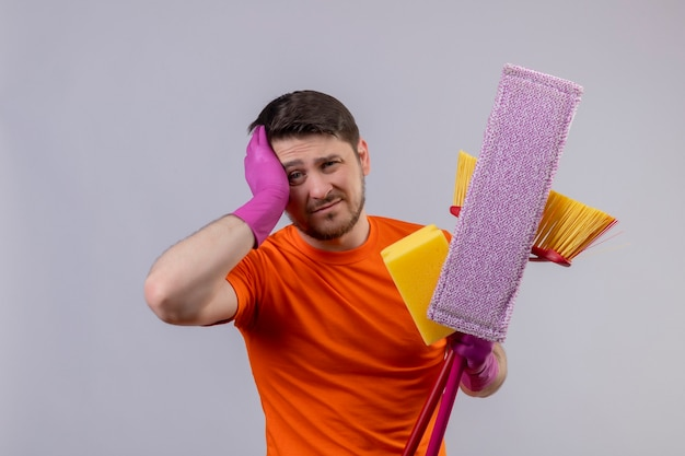 Young man wearing orange t-shirt and rubber gloves holding cleaning tools looking tired and bored with sad expression on face standing over white wall