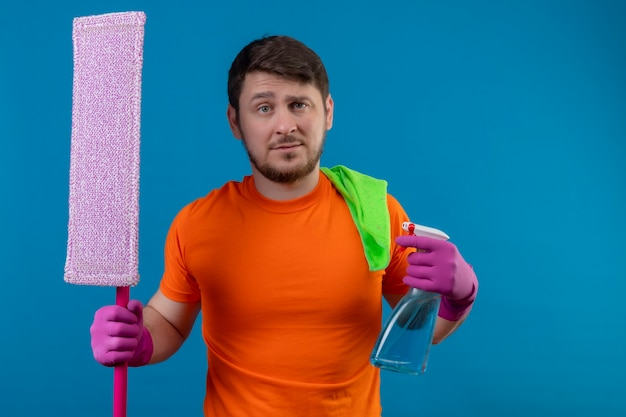 Young man wearing orange t-shirt and rubber gloves holding mop and cleaning spray with skeptic expression on face standing over blue wall