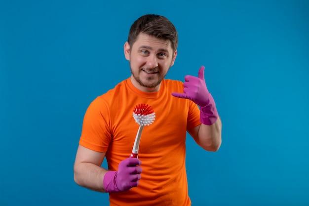 Giovane uomo che indossa la maglietta arancione e guanti di gomma tenendo la spazzola