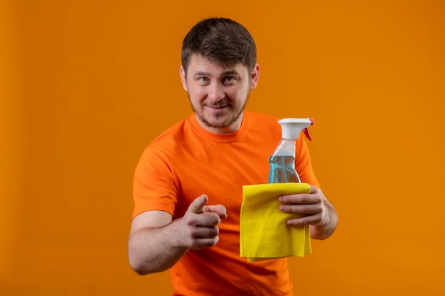 Giovane uomo che indossa la maglietta arancione e guanti di gomma che punta alla telecamera con il dito che tiene la pulizia spray e tappeto