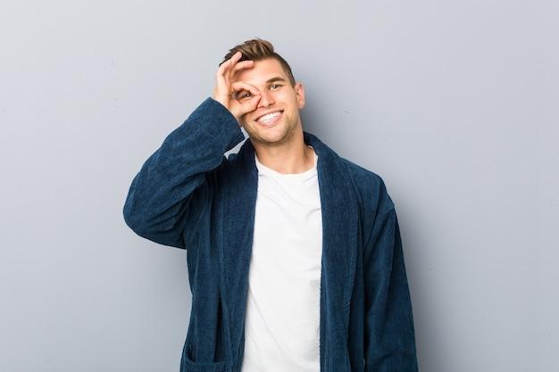Young man wearing pajama excited keeping ok gesture on eye