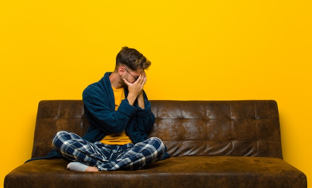 Young man wearing pajamas covering eyes with hands with a sad, frustrated look of despair, crying, side view . sitting on a sofa