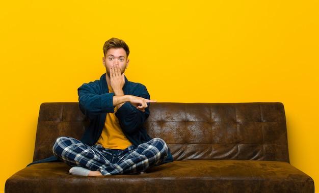 幸せ、ショック、驚きを感じ、手で口を覆って横方向のコピースペースを指しているパジャマを着ている若い男。ソファに座って