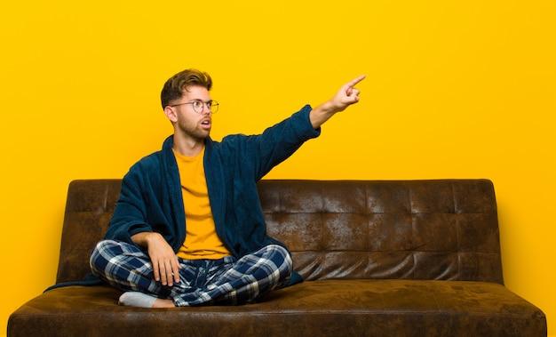 Молодой человек в пижаме, чувствуя себя потрясенным и удивленным, указывая и глядя вверх в благоговении с удивленным открытым ртом. сидя на диване