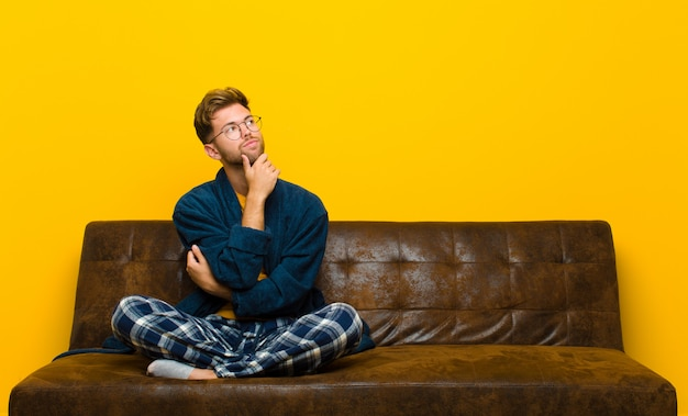 Young man wearing pajamas feeling thoughtful, wondering or imagining ideas, daydreaming and looking up to copy space . sitting on a sofa