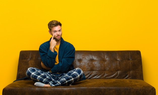 Young man wearing pajamas keeping an eye on you, not trusting, watching and staying alert and vigilant . sitting on a sofa