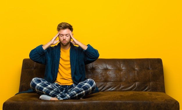 Young man wearing pajamas looking concentrated, thoughtful and inspired, brainstorming and imagining with hands on forehead . sitting on a sofa