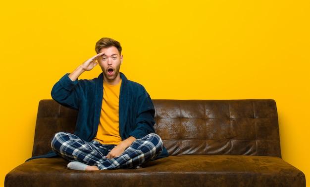 幸せそうに見えるパジャマを着た若い男は、驚いて驚いて、笑顔で、驚くべき、信じられないほどの良いニュースを実現します。ソファに座って
