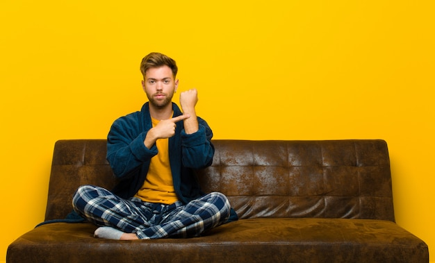 Young man wearing pajamas looking impatient and angry, pointing at watch, asking for punctuality, wants to be on time . sitting on a sofa