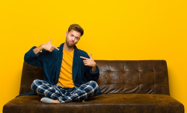 Молодой человек в пижаме выглядит гордым, высокомерным, счастливым, удивленным и удовлетворенным, указывая на себя, чувствуя себя победителем. сидя на диване