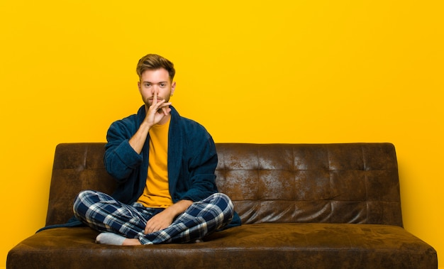 Young man wearing pajamas looking serious and cross with finger pressed to lips demanding silence or quiet, keeping a secret . sitting on a sofa