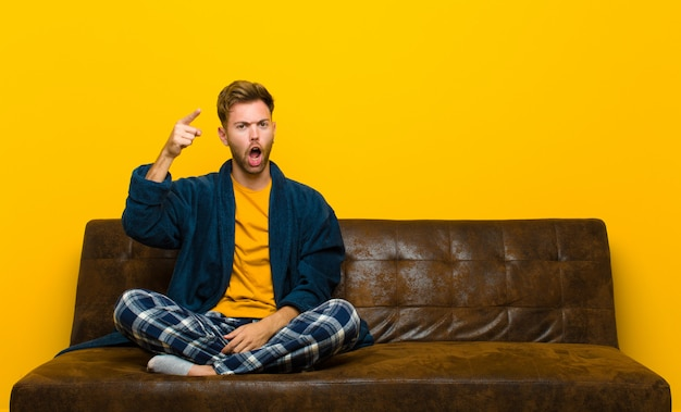 Young man wearing pajamas pointing at camera with an angry aggressive expression looking like a furious