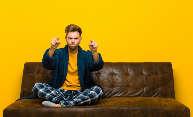 Young man wearing pajamas pointing forward  with both fingers and angry expression, telling you to do your duty . sitting on a sofa