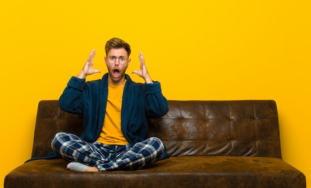 Young man wearing pajamas screaming with hands up in the air, feeling furious, frustrated, stressed and upset . sitting on a sofa