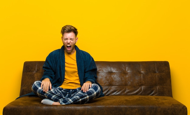 Young man wearing pajamas shouting aggressively, looking very angry, frustrated, outraged or annoyed, screaming no . sitting on a sofa