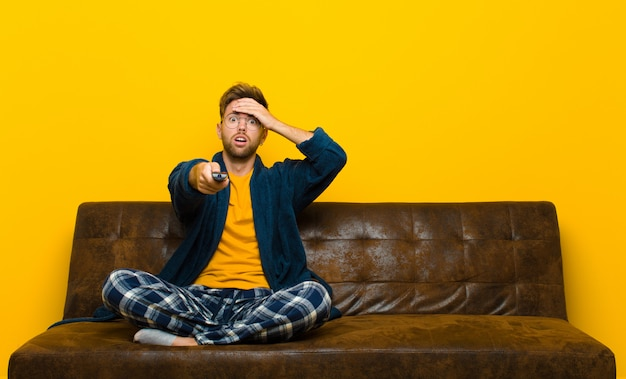 Young man wearing pajamas and sitting on a sofa with a remote control