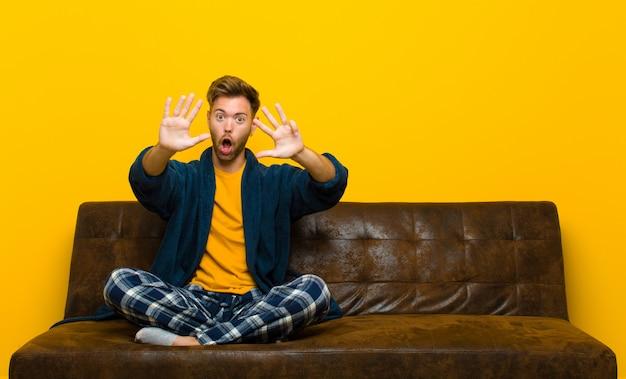 笑みを浮かべて友好的なパジャマを着ている若い男