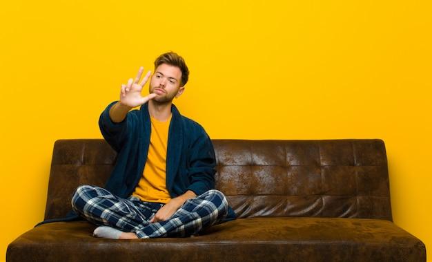 笑みを浮かべて、フレンドリーに見えるパジャマを着た若い男
