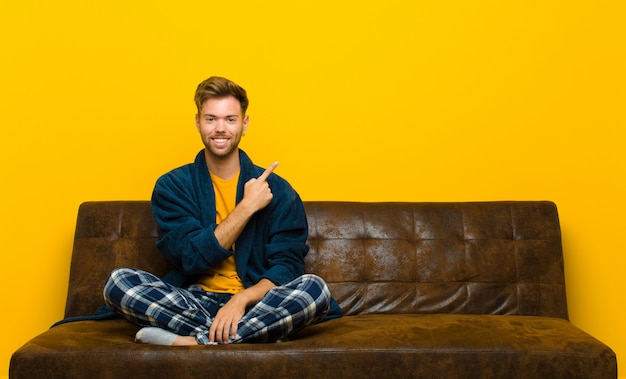 Young man wearing pajamas smiling cheerfully, feeling happy and pointing to the side and upwards, showing object in copyspace . sitting on a sofa