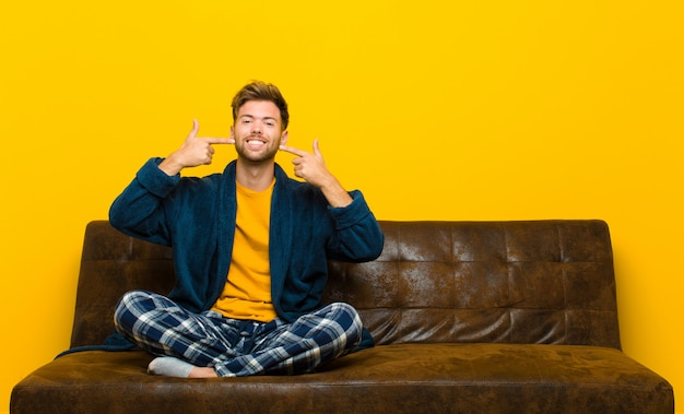 自信を持って自分の幅広い笑顔を指している笑顔のパジャマを着た若い男、肯定的なリラックスした満足した態度。ソファに座って