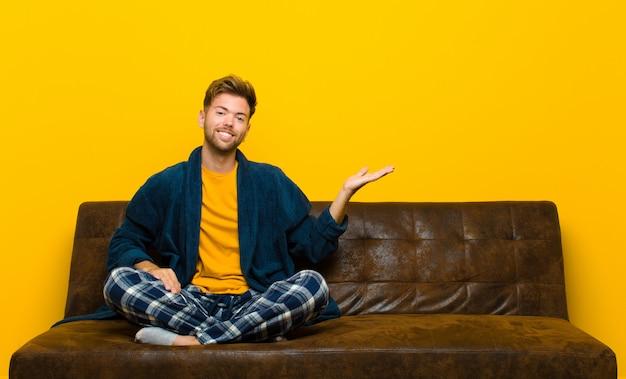 笑みを浮かべて、自信を持って、成功と幸せを感じて、側のcopyspaceの概念やアイデアを示すパジャマを着ている若い男。ソファに座って