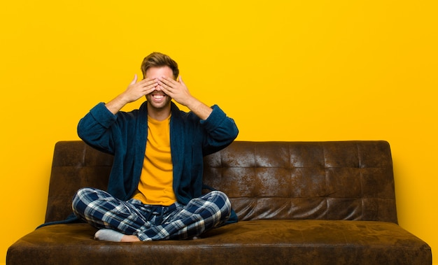 Young man wearing pajamas smiling and feeling happy, covering eyes with both hands and waiting for unbelievable surprise . sitting on a sofa