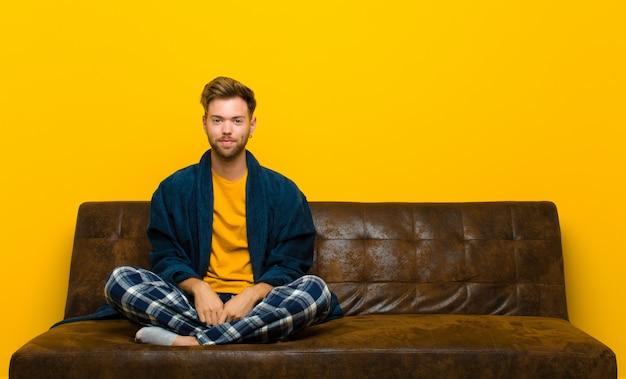 積極的かつ自信を持って笑顔、満足、フレンドリーで幸せそうに見えてパジャマを着ている若い男