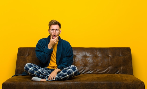Young man wearing pajamas with mouth and eyes wide open and hand on chin, feeling unpleasantly shocked, saying what or wow . sitting on a sofa