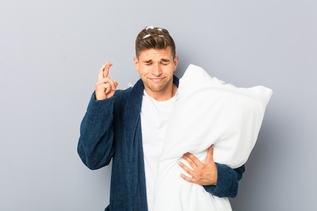 Young man wearing pijama holding a pillow crossing fingers for having luck