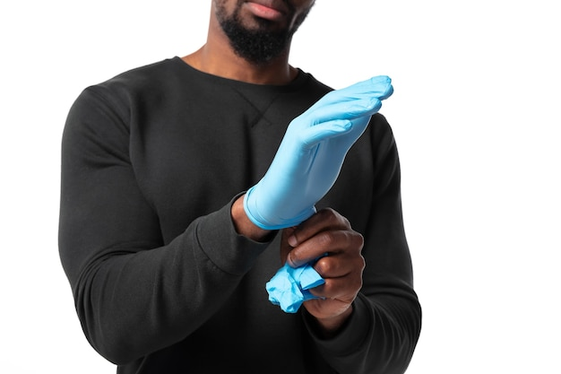 Young man wearing protective gloves on white wall