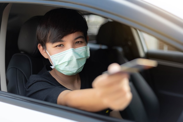 A young man wearing protective mask used credit card for payment at drive thru food service. outbreak covid-19, medical, healthcare and quarantine concept.