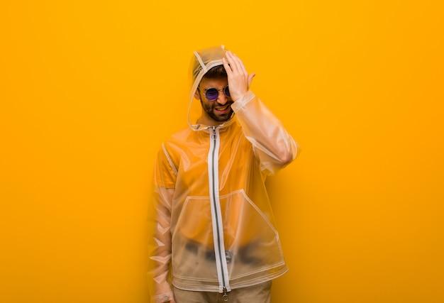 Young man wearing a rain coat forgetful, realize something