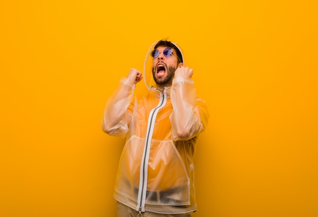 Young man wearing a rain coat screaming very angry and aggressive