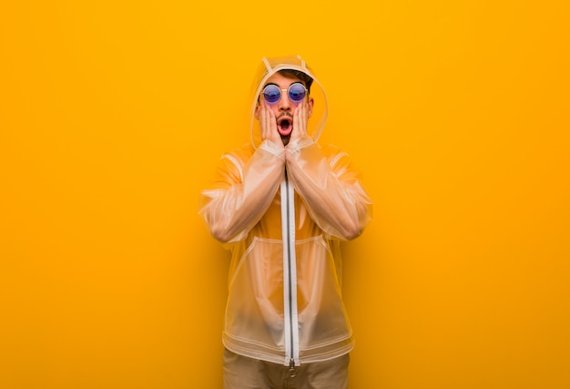 Young man wearing a rain coat surprised and shocked