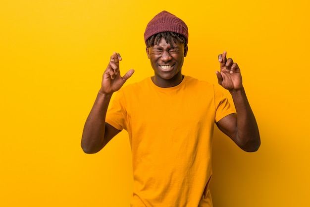 Young man wearing rastas over yellow background crossing fingers for having luck