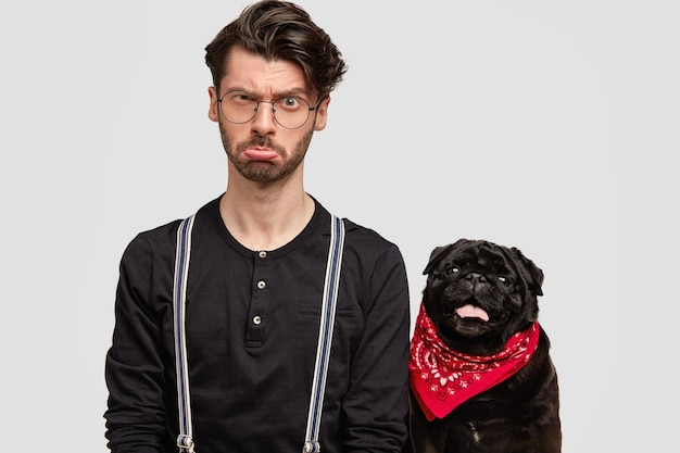赤いバンダナと黒いシャツを着た若い男と彼の犬