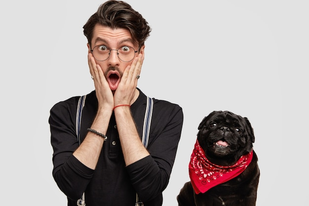 Young man wearing red bandana and black shirt and his dog